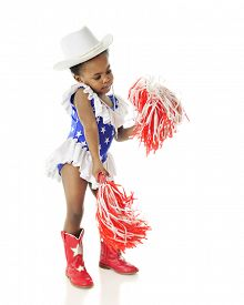 stock photo of pom poms  - An adorable two year old shaking her pom poms while wearing a red - JPG