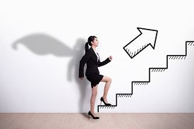stock photo of step-up  - Superhero Business woman stepping up on stairs to gain her success with white wall background asian - JPG