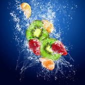 Water drops around fruits on blue background