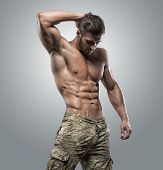 Muscular Athlete Bodybuilder Man On A Gray Background poster