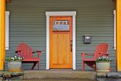 image of front door  - Mission style Stained wood front door with beveled glass surrounded by two Adirondack chairs and flowers - JPG