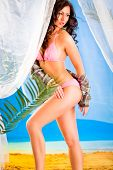 Vogue style photo of sensual girl in bikini posing in summerhouse on beach. Retouched