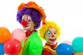 stock photo of birthday party  - portrait of two children dressed as colorful funny clowns with balloons over white background - JPG
