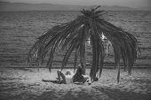Sexy Couple. Topless Woman And Man Lie Under Umbrella Made Out Of Dried Palm Leaves. Couple On Vacat poster