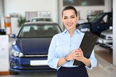 Portrait Of Young Saleswoman In Car Dealership poster
