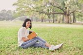 Education Concepts. Asian Women Reading Books In The Park. Beautiful Women Are Relaxing In The Park. poster