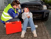 Paramedic caring for an injured woman after a car accident