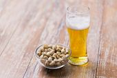 food and drinks concept - glass of draught beer and pistachio nuts on table poster