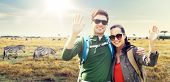 travel, hiking, backpacking, tourism and people concept - happy couple with backpacks waving hands o poster