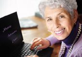 Senior woman portrait, typing on laptop and smiling great at camera. With text on laptop: