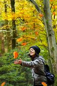 Beautiful smiling woman is catching falling leaves in the autumnal forest