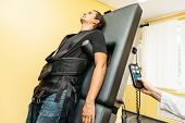 Man On Treatment Recovery Physiotherapy Of Human Spine By Stretching With Special Medical Equipment  poster