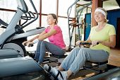 Two happy senior women training on rowing machines in contemporary leisure center poster