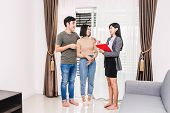Real Estate Agent Holding Document And Talk With Young Couple In A House For Sale. Business And Real poster