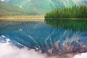 Serene scene by the mountain lake in Canada with reflection of the rocks in the calm water. poster