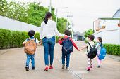 Group Of Preschool Student And Teacher Holding Hands And Walking To Home. Mom Bring Her Children Go  poster