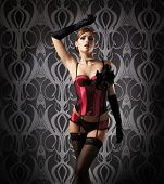 stock photo of redheaded  - Young and beautiful redhead cabaret dancer over vintage background - JPG