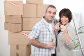 Couple celebrating moving in with champagne