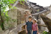 Poor And Neschatnye Children On The Ruins Of A Burnt House. The Brothers Suffered A Natural Disaster poster