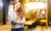 Beautiful young redhead woman thinking and looking up expressing doubt and wonder at night poster