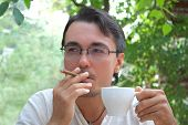 Young Man Smoking Cigar And Drinking Coffee