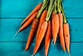 Organic Carrots Over Rustic Wooden Background Closeup. Top View Of Organic Vegetables. poster