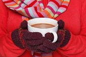 Close up midriff photo of a woman wearing a red jumper, woolen gloves and a scarf holding a mug full