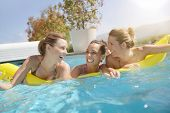 Friends having fun with pool air mattress in swimming-pool poster