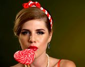 Woman eating lollipops. Girl in pin-up style hold striped candy. Pin up retro female style. Female w poster