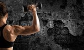 Athletic Muscular Woman Training Biceps With Dumbbells On Grunge Background poster