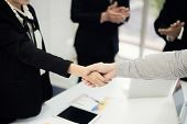Business People Shaking Hands, Finishing Up A Meeting To Seal A Deal With His Partner Business With  poster