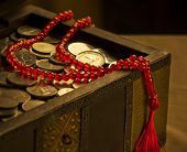 UAE Dirham coins in a trunk and a rosary