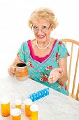 Smiling senior lady cheerfully takes her prescriptions and suppliments.  White background.