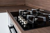 A Modern Gas Cooker With Ceramic Hob, Electric Oven And A Dark Brown Wooden Kitchen Ready For Cookin poster