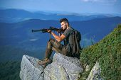 Hunting Licenses. Illegal Hunting Poacher In The Forest. Handsome Hunter Man Holding Gun And Walking poster