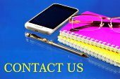 Contact Us-business Contacts. A Written Message On The Background Of A Smartphone, A Notepad, Glasse poster