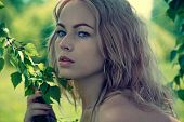 picture of green leaves  - Fashion portrait of young beautiful blond woman in forest - JPG
