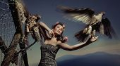 Fashionable photo of a woman holding eagle