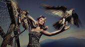 Fashionable photo of a woman holding eagle