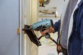 Carpenter Using Air Nail Gun Installation Of Install In The New Door poster