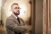 Young Bearded Man In Eyeglasses Standing With His Arms Crossed And Looking At Beautiful Picture poster