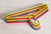 Five Multicolored Plastic Clothes Hangers On A Light Wooden Surface. Set Of New Colorful Plastic Clo poster