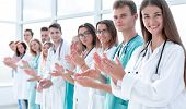 group of smiling young doctors applauds standing in a row poster