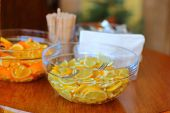 Sliced lemons In A Glass Bowl, Standing On A Table Next To A Transparent Bowl With Slices Of Orang poster