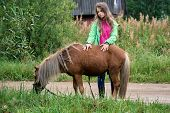 Teenage Girl Stands With A Pony Colt At Countryside poster