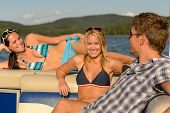 Sunbathing young friends lying and talking on yacht summer