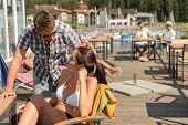 Young couple talking at bar beside beach summer terrace