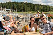 Young people enjoying summer vacation sunbathing drinking at beach bar