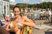 Woman with wet hair drinking cocktail sitting at beach bar