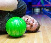 Bizarre drunk man lying on bowling alley